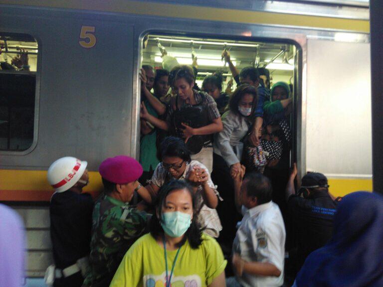 Penumpang menyerbu untuk turun di stasiun Pondok Cina di emplasemen tanpa peron. Tampak Walka dan petugas PT KCJ yang membantu.