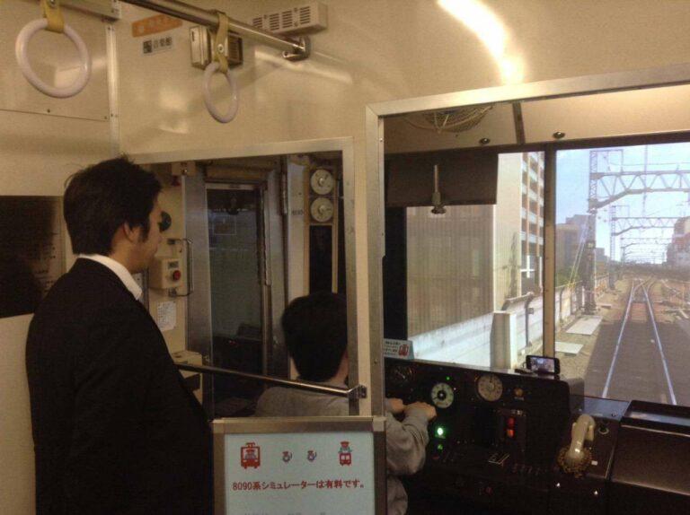 Salah satu pengunjung yang mencoba bermain di Simulator KRL seri 8090. Dipantau oleh staf produsen simulator, Ongakukan.